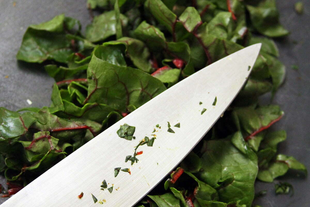 A knife lies onto of a bed of rhubarb chard after a thorough slicing.