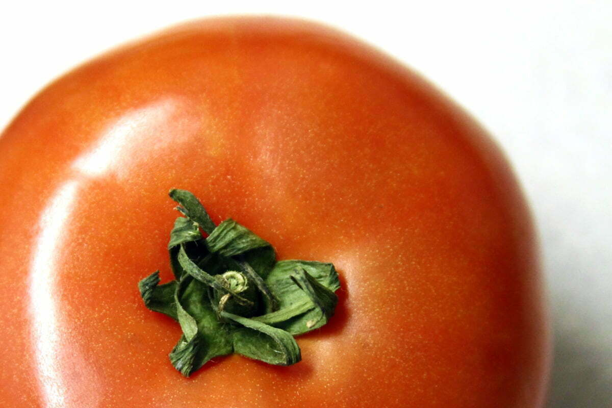 A close-up photograph of a bright red tomato with a green stem.