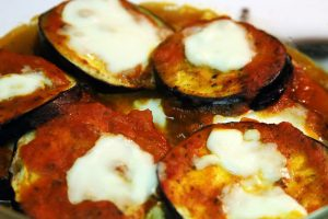 The fully baked eggplant slices finish topped with hot mozzarella cheese and tomato sauce.