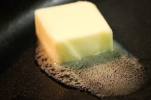 A big piece of butter starts to melt in a hot cast iron skillet.