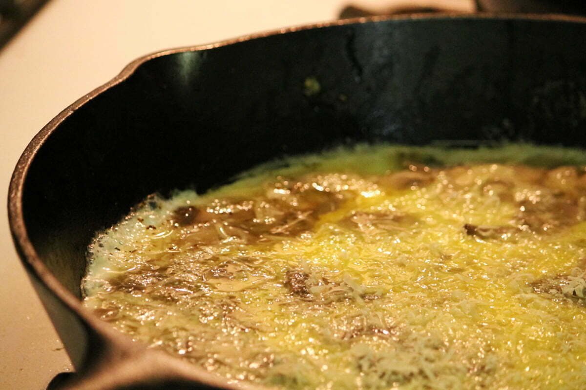 A frittata starting to cook in a hot cast iron skillet.