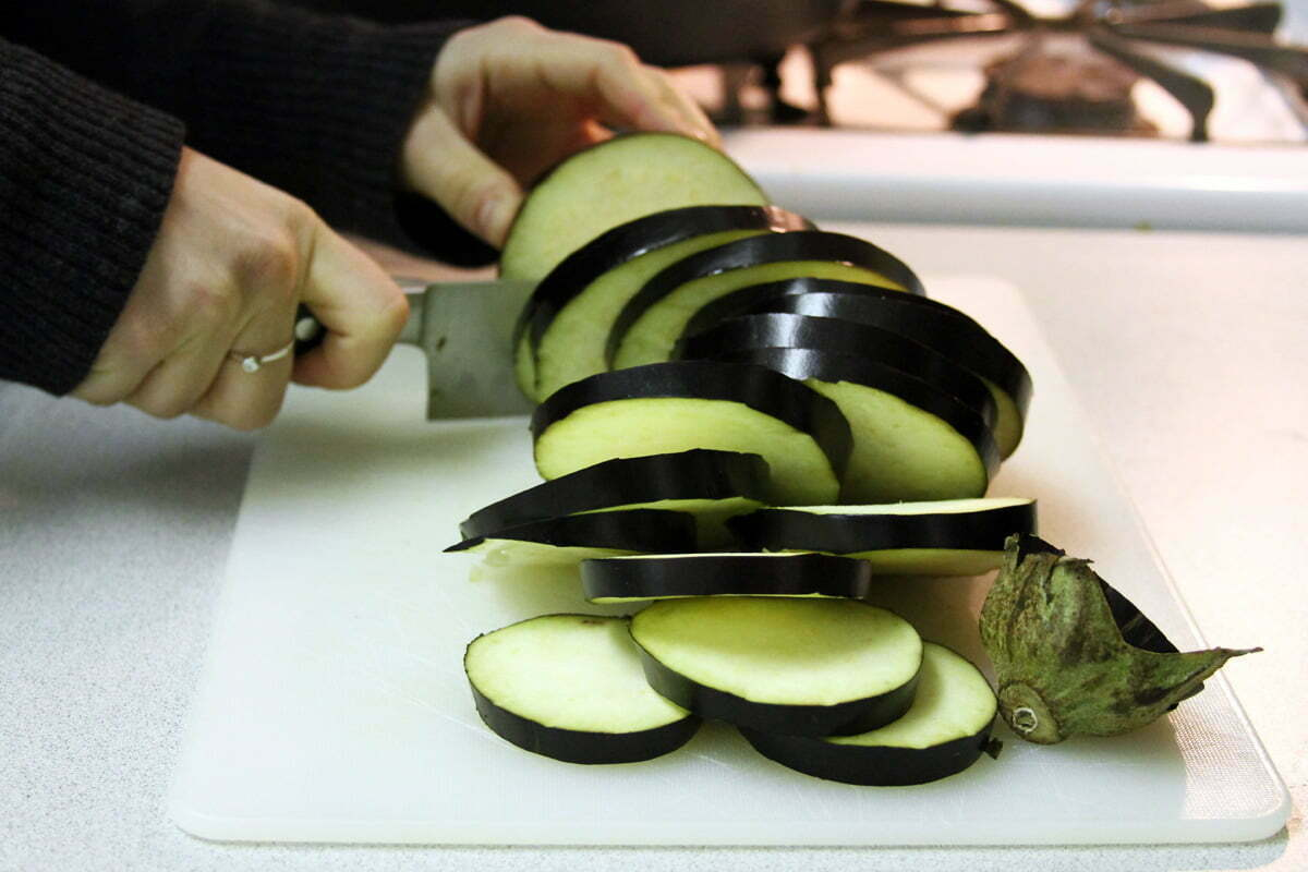 An eggplant is sliced on the cutting board.