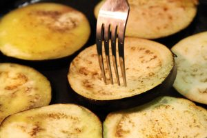 A fork turns slices of eggplant cook in a cast-iron pan.