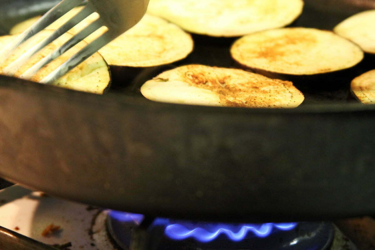 A cast iron skillet sits on a blue hot flame and cooks some pieces of eggplant.