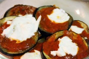 Mozzarella cheese is added to the eggplant slices with tomato sauce.