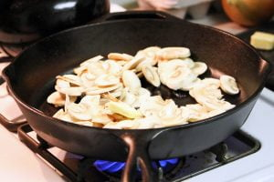 A pile of mushrooms cook in butter on a hot cast iron skillet.