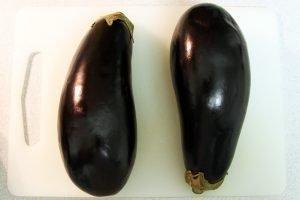 Two large dark purple eggplants sit side-by-side on a cutting board.