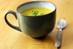 A side angle of a bowl filled with butternut squash soup and a spoon on a wooden table.