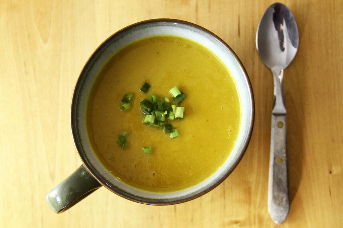 A large cup of butternut squash soup with a spoon on a wooden table, seen from above.