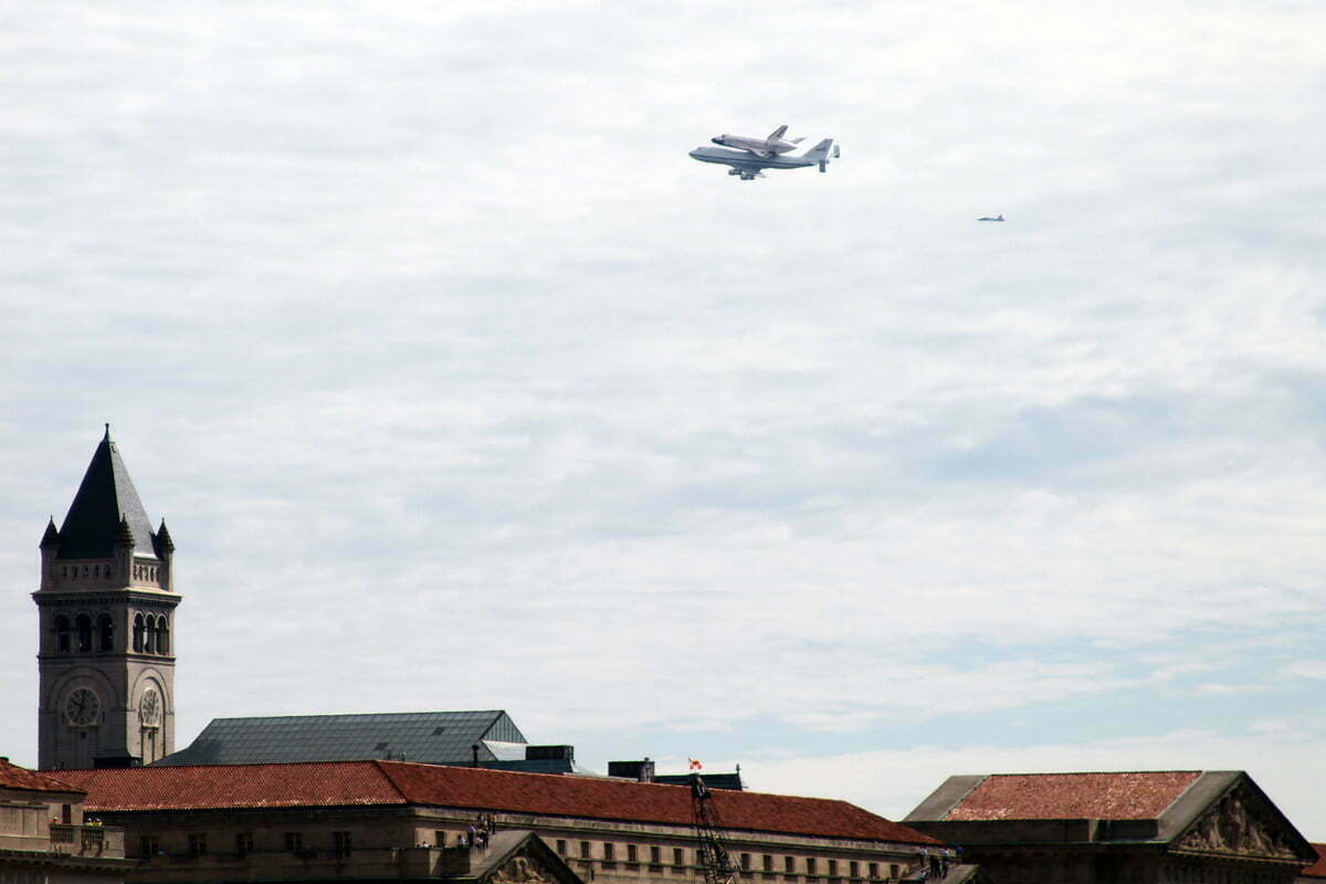 The space shuttle Discovery flying over the Old Post Office Building in Washington DC.