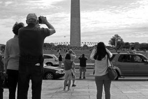 A crowd of people stop to photograph and watch the Space Shuttle Discovery flying by the Washington Monument.