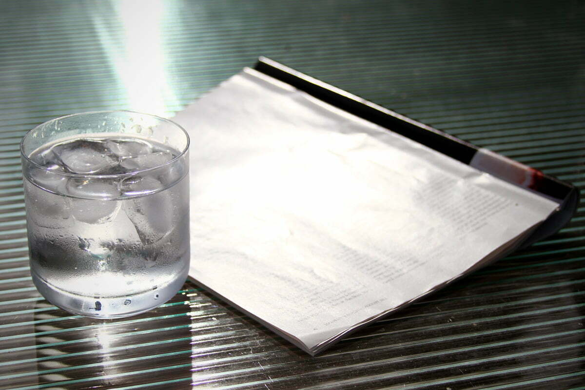 A magazine and glass of water sit on a table in the summer sun.