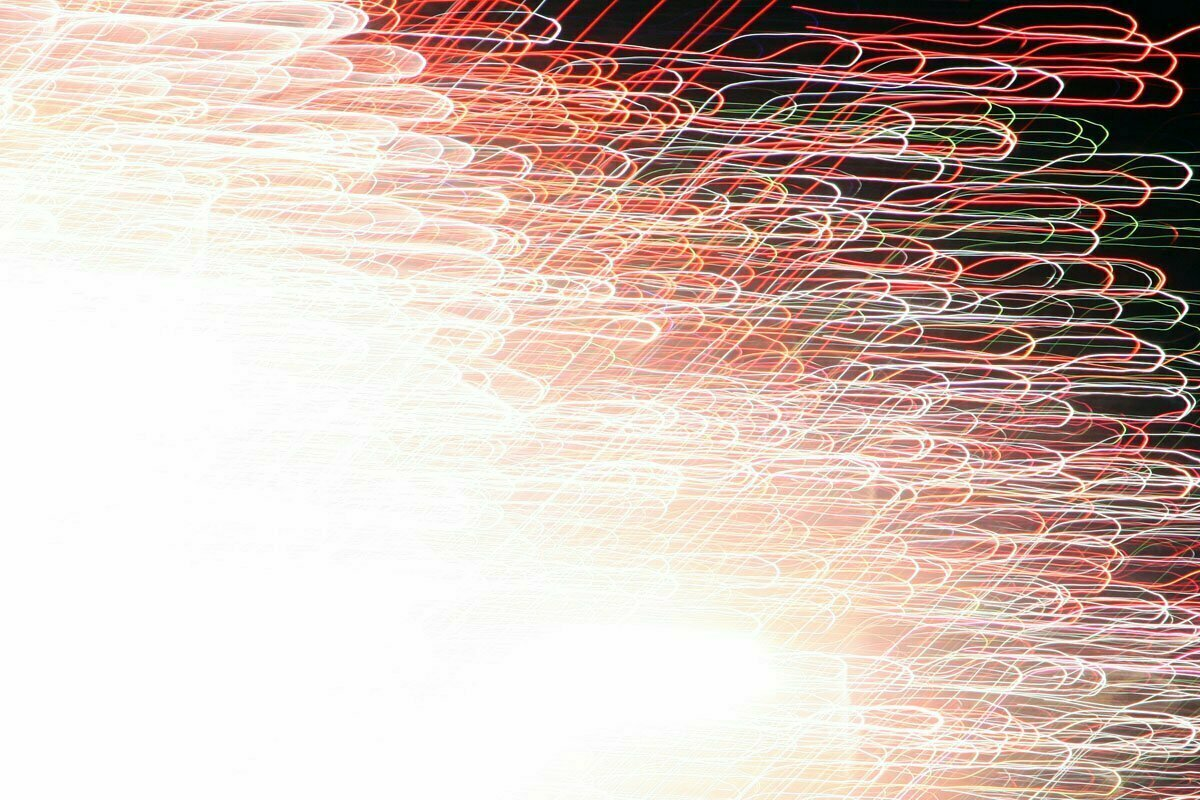A long exposure photograph of fireworks with blurry colorful lines going in many directions.