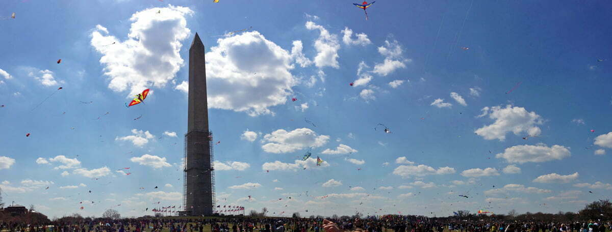 A panorama of kites in the air and the crowds near the Washington Monument at the annual Cherry Blossom Kite Festival on the National Mall in Washington D.C.