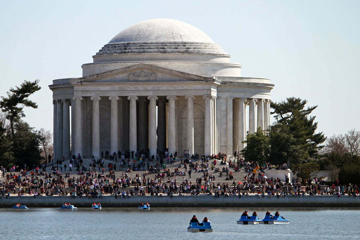 The Thomas Jefferson Memorial packed with tourists and paddle boats during the cherry blossom festival at the Tidal Basin in Washington D.C.