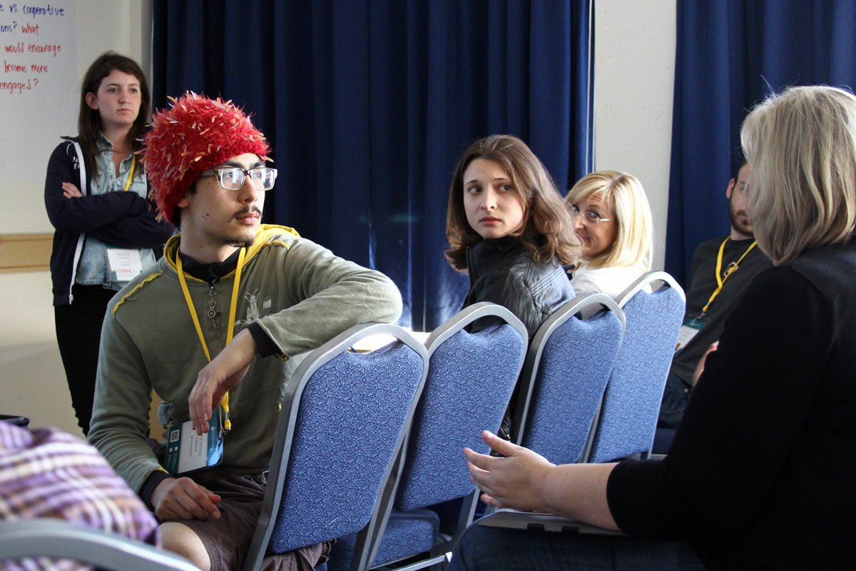 A group of conference goings have a passionate and engaged conversation in a meeting room.