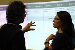 A photograph of two people in conversation in front of a projector screen at the Sunlight Foundation's TransparencyCamp.