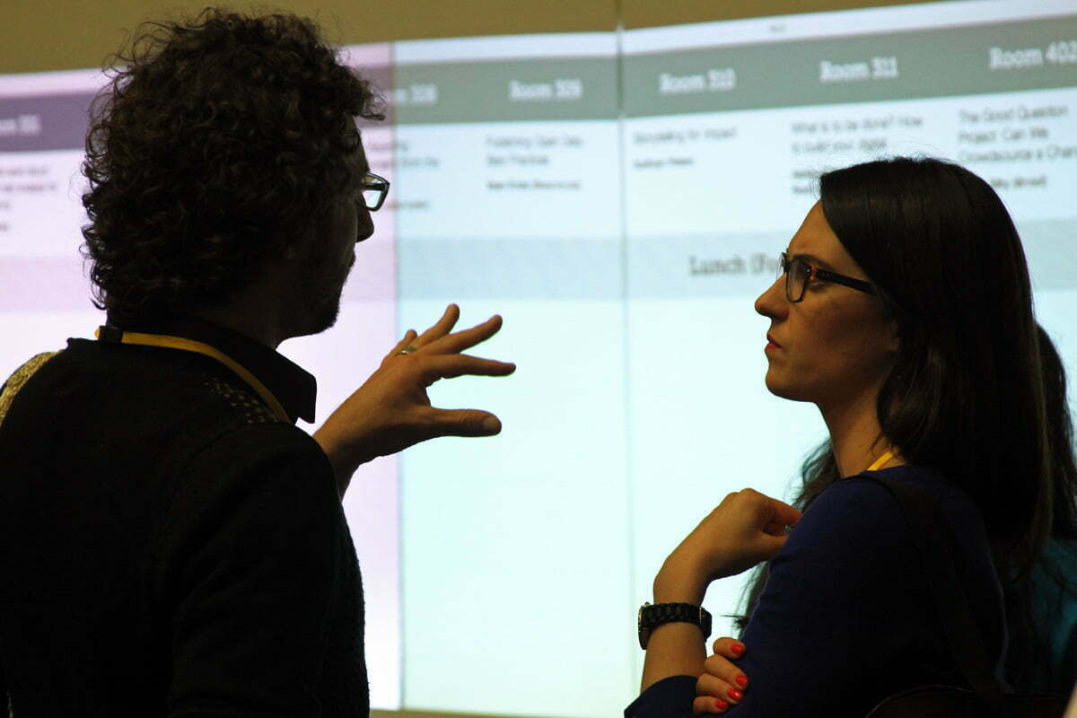 A photograph of two people in animated conversation in front of a projector screen at the Sunlight Foundation's TransparencyCamp.