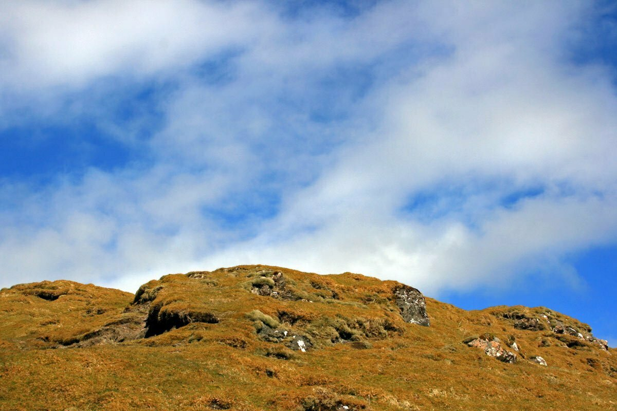 Yellowing peat moss covers a rocky hill against a cloudy blue sky in the Scottish Highlands.
