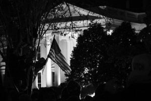 An Obama supporter hoists an American flag in the air at the White House in Washington DC following the reelection of the president in 2012.