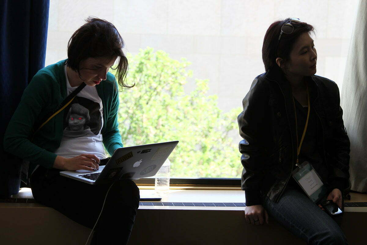 Two female TransparencyCamp attendees listen to a session and work on a laptop near a bright window.