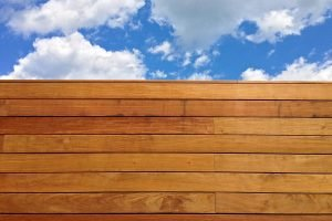 Photograph of a blond wooden wall with a cloud filled blue sky in the background.