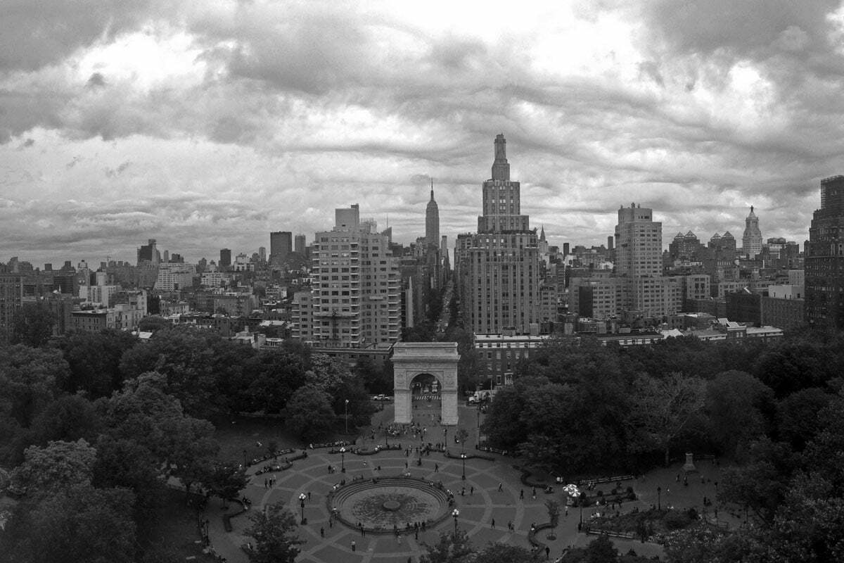 A black and white skyline view of New York City over Washington Square Park on an overcast day.