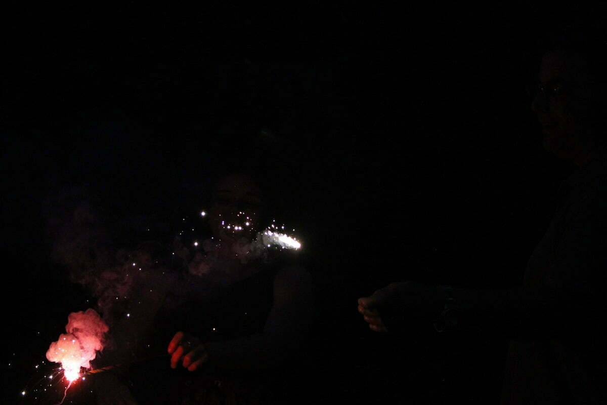 A photograph of a puff of colorful smoke and sparks come off two sparklers at a picnic.
