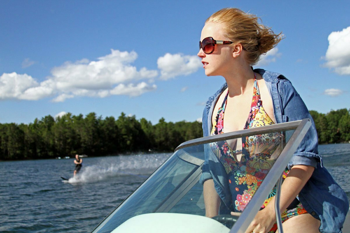Nina stands and drives the boat on the lake while Will water skis in the background.