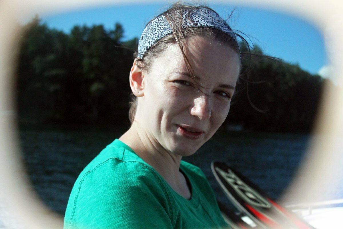 Sara seen through sunglasses on a summer lake in Wisconsin.