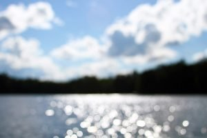 An abstract and out of focus shot of a cloudy sky, shimmering blue water and trees.