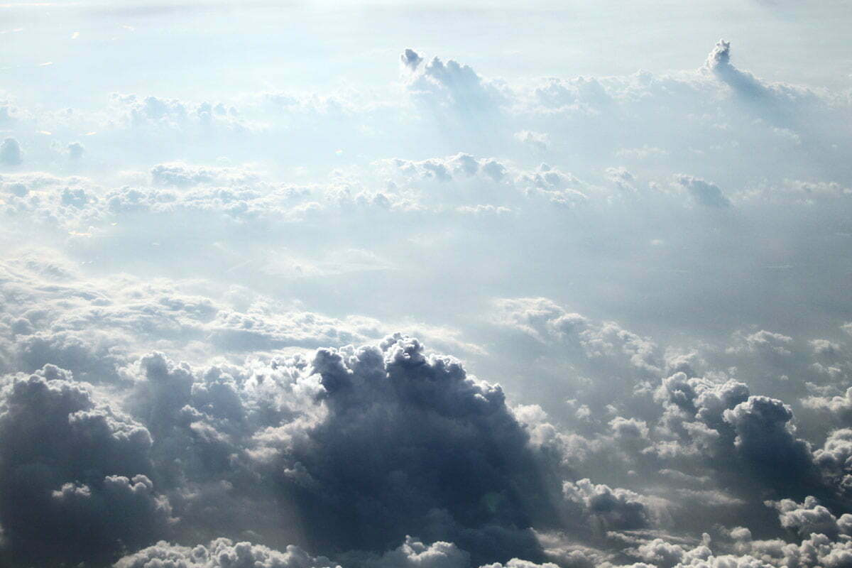 Blue and white cumulus clouds seen from above in a plane.