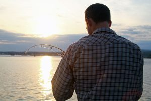 A man with his back to the camera focuses on his fishing line as the yellow sun sets over the water.