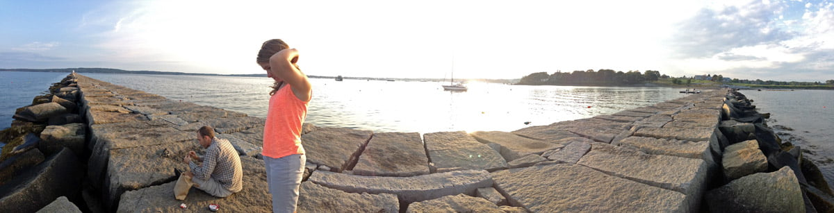 A 180 degree panorama of a man cutting bait as a woman stands ready to fish off the breakwater in Rockport, Maine at sunset.