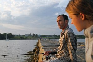A man and woman fish on the breakwater in Rockland, Maine.