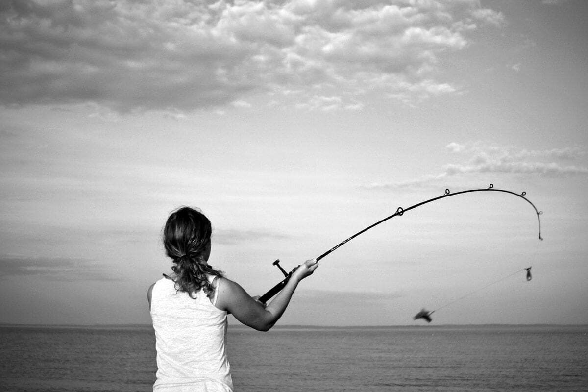 A woman casts the bait on her fishing pole into the water from the breakwater in Maine.