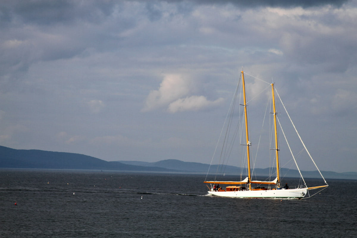 A two masted sailing ship off the coast of Maine with mountains and islands in the distance.