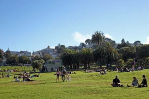 People relax on the green grass at Dolores Park in San Francisco.