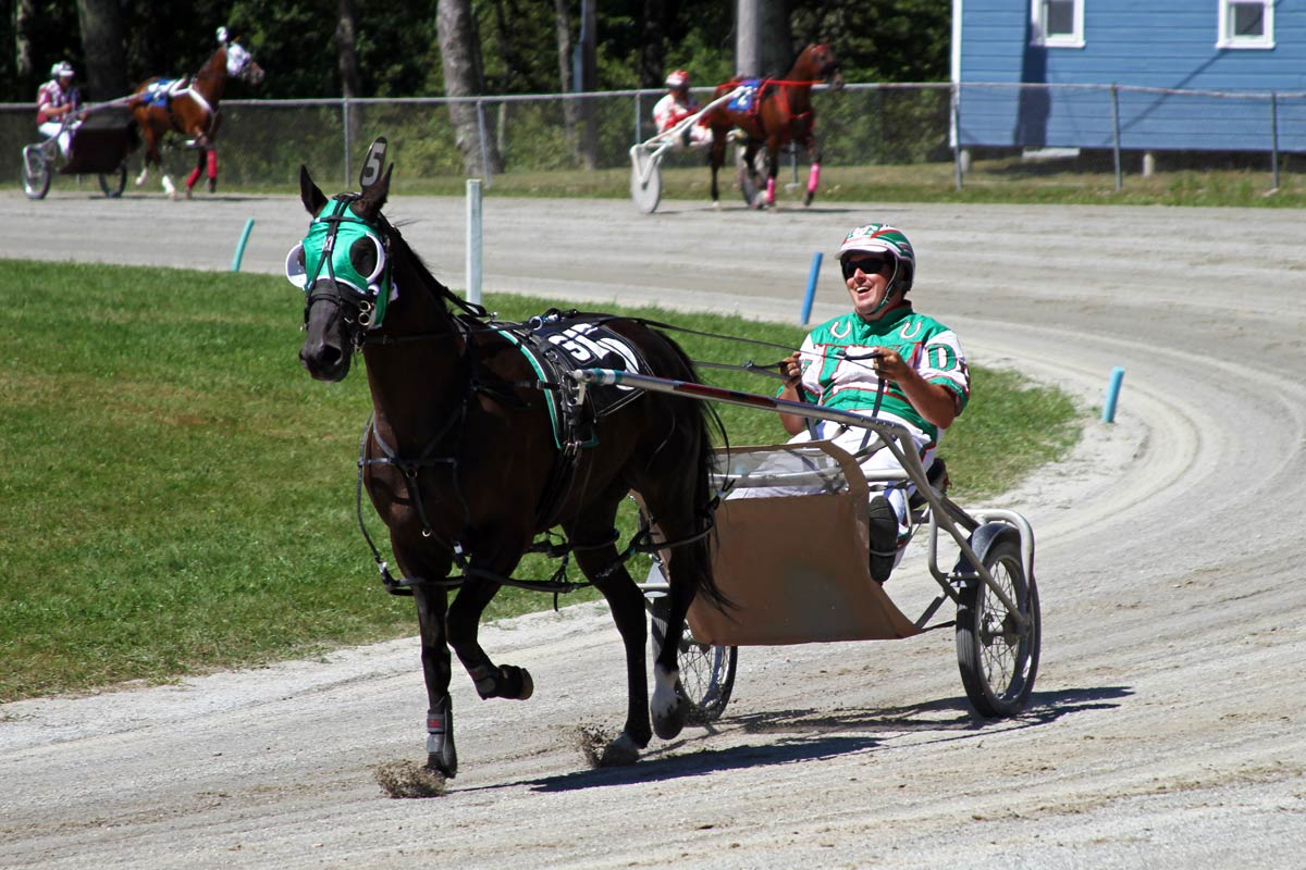A grinning sulky driver in a green outfit drives his horse during a harness race in Maine.