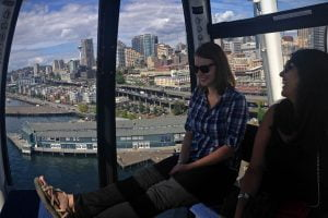 Two friends sit in the Seattle Great Wheel looking over the city from the ferris wheel compartment.