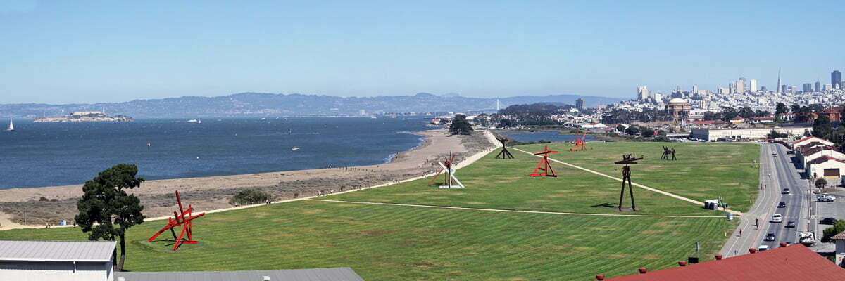A panorama taken from over Crissy Field that shows Alcatraz on the far left and the buildings of downtown San Francisco on the right.