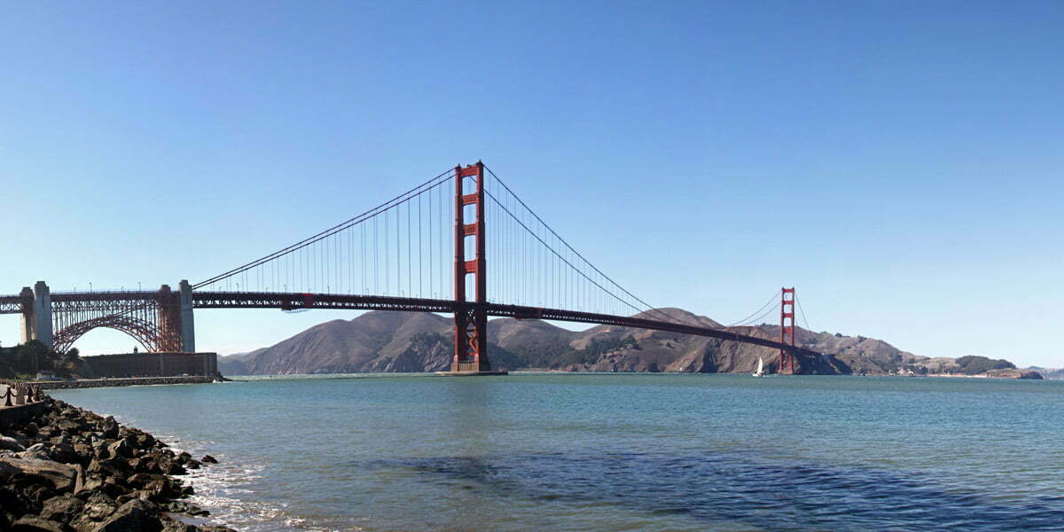 A panoramic image from six different photographs of the Golden Gate Bridge seen from bay level in San Francisco, California.