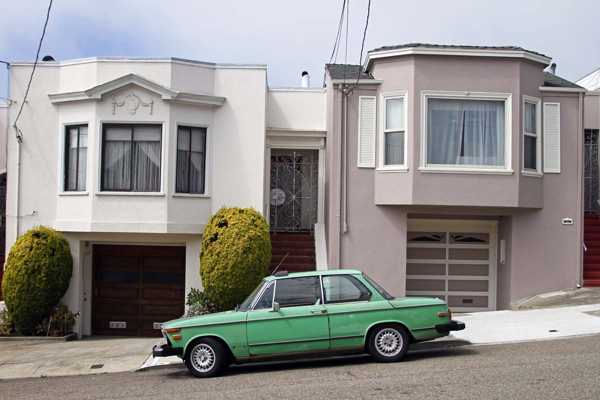 A slanted road in San Francisco with a parked green BMW 2002 sits outside two houses.