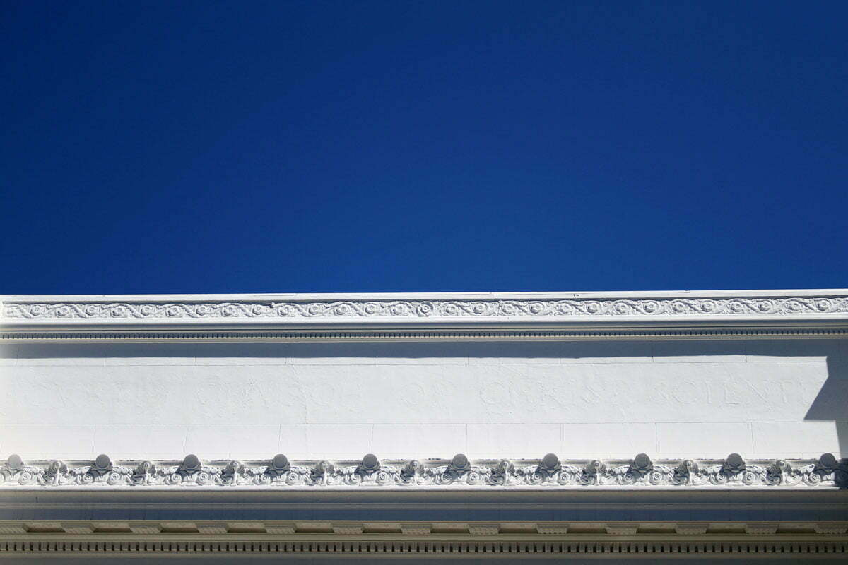 Blue sky against the top portion of the Internet Archive building with the text from the former Fourth Church of Christ, Scientist church white washed out in San Francisco.