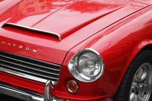 The front section of a red 1967 Datsun Roadster 1600 with the hood scoop, headlight, grill and panasport wheel visible.