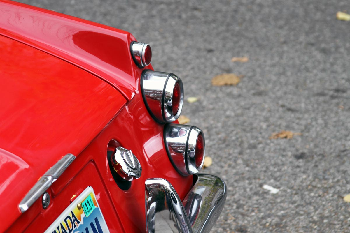 The chrome tail lights on a red 1967 Datsun Roadster 1600.