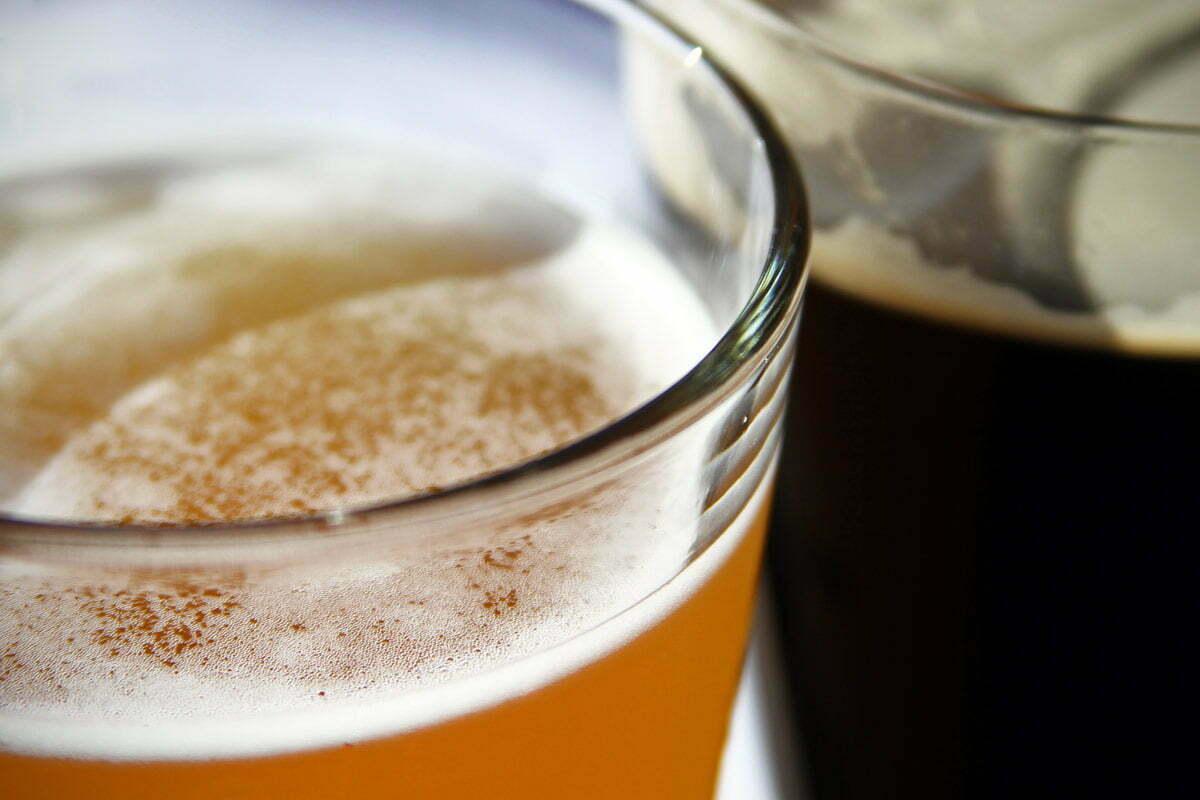 A glass of hefeweizen wheat beer and dark porter beer.