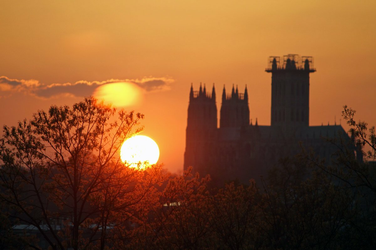 A photo of a large orange sun setting between trees and the National Cathedral in Washington DC.