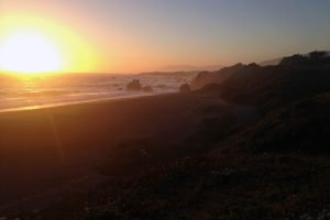 A sunset over the Pacific ocean along a beach with rocks out in Bodega Bay at Sonoma, California.