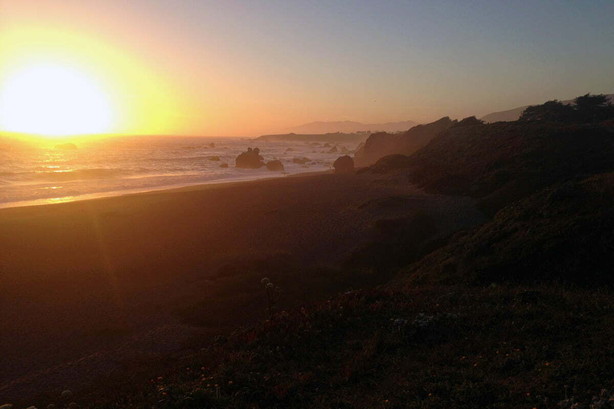 A sunset over the Pacific Ocean along the beach and rocks out in waters of Bodega Bay at Sonoma, California.